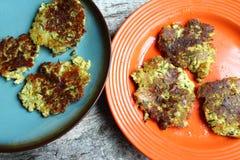 Platten von Blumenkohl-und Brokkoli-Pfannkuchen auf Holztisch Stockbild