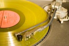 Plattenspieler mit gelber Langspielplatte Stockbilder