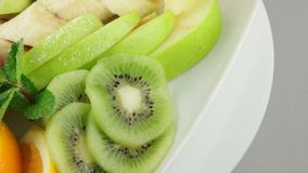 Platter of a assorted fresh fruits. In long white plate stock footage