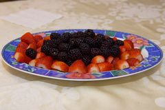 Platter of black berries and strawberries. A large fruit platter on a table, containing black berries and strawberries stock image