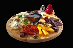 Platter of cheeses, sausages and nuts Stock Photo