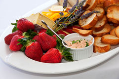 Platter with cheeses and strawberries Royalty Free Stock Images