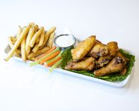 Platter of chicken wings and french fries stock photography