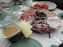 Platter of cold cuts with rustic ham prosciutto, salami, lard, cheese and olives . Tuscany, Italy Stock Images