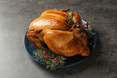 Platter of cooked turkey with cranberry and fir tree branches. On grey background royalty free stock photo