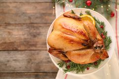 Platter of cooked turkey with garnish and Christmas decoration on wooden background, top view. Space for text royalty free stock photos