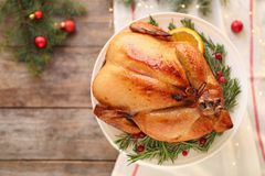 Platter of cooked turkey with garnish and Christmas decoration on wooden background, top view. Space for text royalty free stock photo