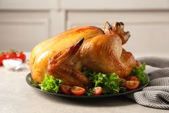 Platter of cooked turkey with garnish. On table stock photo
