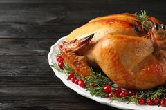 Platter of cooked turkey with garnish on table, closeup. Space for text stock image