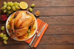 Platter of cooked turkey with garnish on wooden background, flat lay. Space for text royalty free stock photography