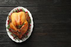 Platter of cooked turkey with garnish on wooden background, top view. Space for text royalty free stock image