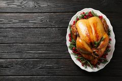 Platter of cooked turkey with garnish on wooden background, top view. Space for text stock image