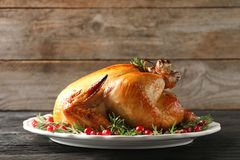 Platter of cooked turkey with garnish. On wooden table stock image