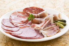 Platter of different ham Meat, salami and gherkin Stock Images
