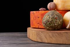 Platter with different types of cheese and nuts. Handmade cheese on wooden board. cheese production Royalty Free Stock Photography