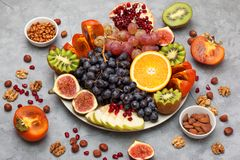 Platter with fresh fruits and nuts. Orange, grapes, kiwi, persimmons, figs, almonds, walnuts, pine nuts on a grey background Stock Photo