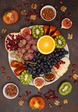 Platter with fresh fruits and nuts. Orange, grapes, kiwi, persimmons, figs, almonds, walnuts, pine nuts on a dark background Royalty Free Stock Images