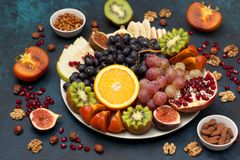Platter with fresh fruits and nuts. Orange, grapes, kiwi, persimmons, figs, almonds, walnuts, pine nuts on a blue background Royalty Free Stock Images