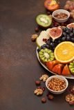 Platter with fresh fruits and nuts. Orange, grapes, kiwi, persimmons, figs, almonds, walnuts, pine nuts on a dark background Royalty Free Stock Photo