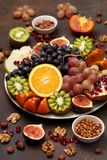 Platter with fresh fruits and nuts. Orange, grapes, kiwi, persimmons, figs, almonds, walnuts, pine nuts on a dark background Stock Photo