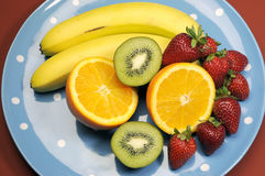 Platter of fruit - bananas, orange, kiwi fruit and strawberries Stock Photos