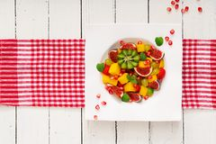 Platter fruits and berries. Mango, kiwi, fig, strawberry, grapes, pear and orange. Vegan cuisine. Dietary menu. Flat lay. Top view Royalty Free Stock Photography