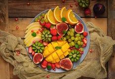 Platter fruits and berries. Mango, kiwi, fig, strawberry, grapes, pear and orange. Vegan cuisine. Dietary menu. Flat lay. Top view Royalty Free Stock Photo