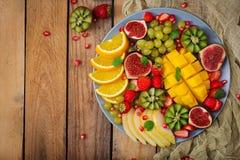Platter fruits and berries. Mango, kiwi, fig, strawberry, grapes, pear and orange. Vegan cuisine. Dietary menu. Flat lay. Top view Royalty Free Stock Image