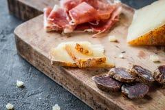 Platter with homemade dried meat salami, sliced Italian hard cheese, ham jamon serrano or Italian prosciutto crudo Royalty Free Stock Photos