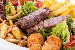 Platter of mixed meats, salad and French fries Stock Images