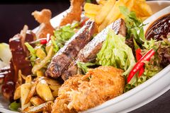 Platter of mixed meats, salad and French fries Stock Photo
