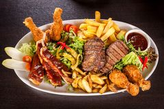Platter of mixed meats, salad and French fries Stock Photos