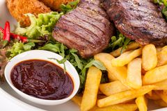 Platter of mixed meats, salad and French fries Royalty Free Stock Image