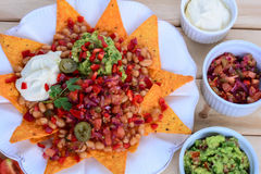 Platter of Nachos with Salsa Jalapenos and Cheese. On plate Stock Photography