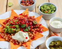 Platter of Nachos with Salsa Jalapenos and Cheese. On plate Stock Image