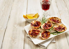Platter of Oysters Kilpatrick with Lemon and Wine Stock Images