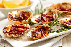 Platter of Oysters Kilpatrick on Table with Lemon Royalty Free Stock Photo