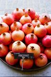 Platter pomegranate fruit for sale at a farmers market. Platter of pink and red pomegranates for sale at a fruit market stock photography
