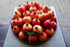 Platter of pomegranate fruit for sale at a farmers market. Platter of pink and red pomegranates for sale at a fruit market stock photos