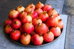 Platter pomegranate fruit for sale at a farmers market. Platter of pink and red pomegranates for sale at a fruit market stock photo