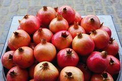 Platter of pomegranate fruit for sale at a farmers market. Platter of pink and red pomegranates for sale at a fruit market stock images