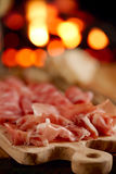 Platter of serrano jamon Cured Meat with cozy fireplace backgro stock photo