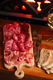 Platter of serrano jamon Cured Meat with cozy fireplace and wine. Background Stock Photos