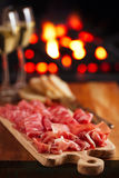 Platter of serrano jamon Cured Meat with cozy fireplace and wine. Background Stock Images