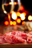 Platter of serrano jamon Cured Meat with cozy fireplace and wine Stock Photography