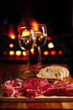 Platter of serrano jamon Cured Meat with cozy fireplace and wine. Background Royalty Free Stock Images