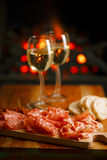Platter of serrano jamon Cured Meat with cozy fireplace and wine. Background Stock Photography