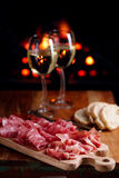 Platter of serrano jamon Cured Meat with cozy fireplace and wine. Background Royalty Free Stock Image