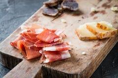 Platter with Spanish ham jamon serrano or Italian prosciutto cru. Do, homemade dried meat salami, sliced Italian hard cheese pecorino toscano, on old wooden Stock Photography