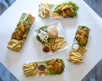 Platters of chicken wings, cheeseburgers, and french fries stock image